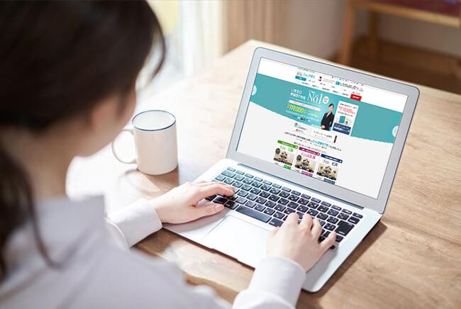 パソコンでネット葬儀を調べる女性のイメージ画像